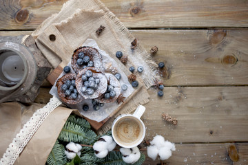 muffins with blueberries on a wooden background, bouquet of branches and coffee in a white mug