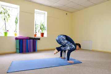 Dark-haired European girl doing warm up in spacious fitness room