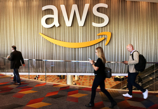 Attendees at Amazon.com Inc annual cloud computing conference walk past the Amazon Web Services logo in Las Vegas
