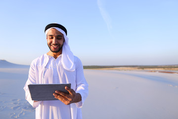 Successful Arabian businessman holds in hands and uses tablet, s