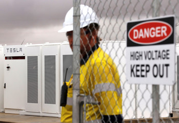 A worker stands next to the main gate of the compound for the Hornsdale Power Reserve, featuring the world's largest lithium ion battery made by Tesla, during the official launch near the South Australian town of Jamestown