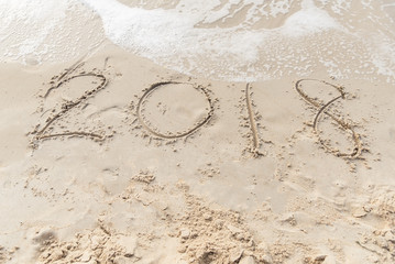 2018 written on sandy beach New Year is coming like date holiday concept.