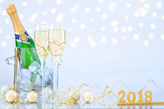 New Year Celebration with Champagne Glasses and a Bottle 2018. New Year flutes with bubbling champagne and a bottle on the blue background with bokeh.