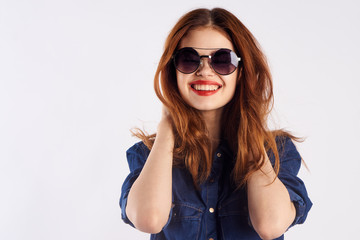 Young beautiful woman on a light background in sunglasses, portrait, smile, blank space for copy