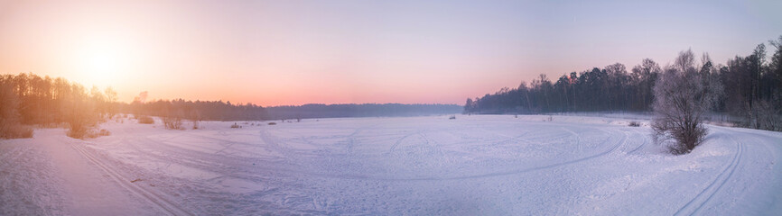 Winter sunset on the frozen lake in park