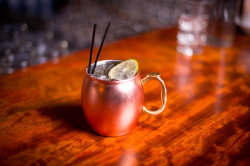 Close up on Moscow mule cocktail in copper mug with wood bar background
