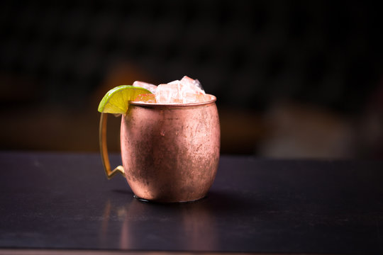 Isolated Moscow mule cocktail overflowing with ice in a copper mug