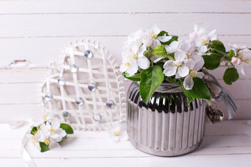 Apple tree flowers in vase and  decorative heart  on white wooden background.