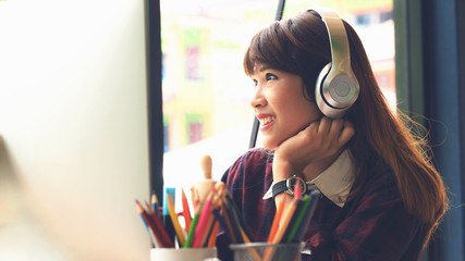 Beautiful young woman designer listening music with headphone for inspiration ideas to working in office background, vintage color tone process