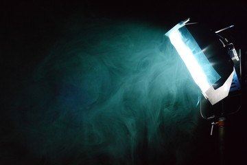 smoke around a filtered light on a film set