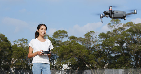 Woman control fly drone in park