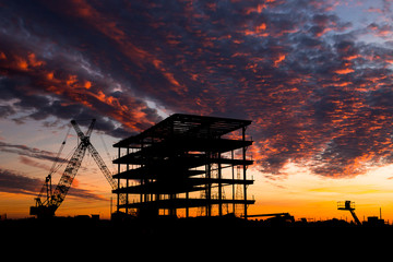 Steel construction site at sunset with a crane.