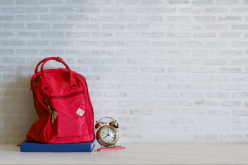 Red backpack and books school supplies on desk.