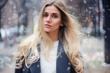 winter portrait of young woman walking on city streets in snowy day, wearing warm grey coat