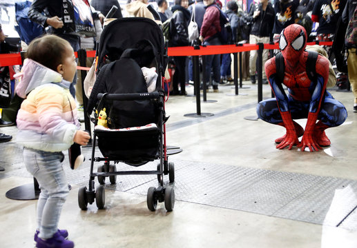 A baby boy cries as a man in a Spider-Man costume poses to him at Tokyo Comic Con at Makuhari Messe in Chiba