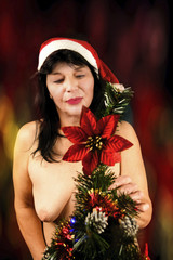 Attraktive Weihnachtsfrau am Weihnachtsbaum