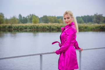 A stylish blonde in a suburb of London walks in drizzly cold weather. Color your bright day with bright colors. Bright stylish cloak on a charming lady