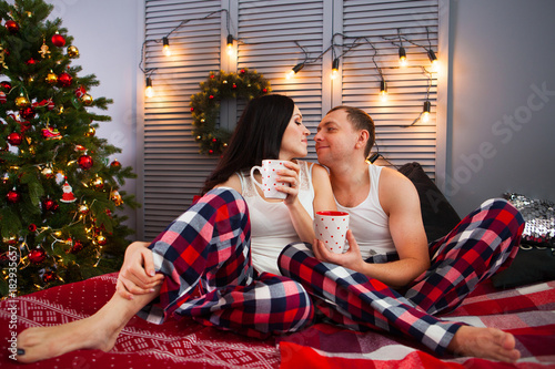 happy new year cheerful beautiful young couple drinking morning coffee in pajamas happy family