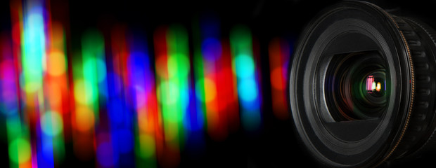 Photo lens and black background with individual light blur