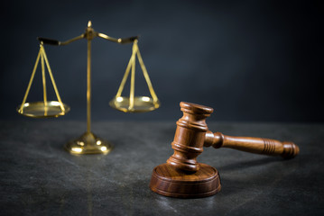 Golden scales of justice, gavel and books on brown background, Law code