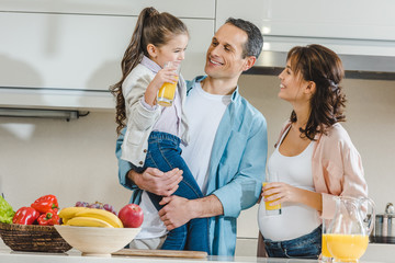 happy family with juice, vegetables and fruits at kitchen looking at each other