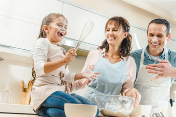 happy family with faces in flour, kid holding whisk and laughing at kitchen