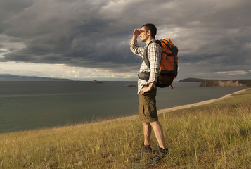 young tourist man with a backpack on the lake, Lake Baikal, summer tourist walk, freedom and happiness