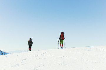 Winter hike in the mountains, two men are walking along the snow ridge.