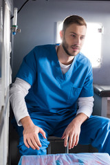 cheerful handsome male doctor sitting in ambulance