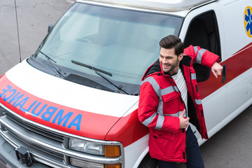 smiling handsome male doctor standing and leaning on ambulance