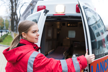 Young female doctor opening ambulance doors and looking away