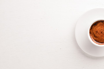 Espresso coffee cup on a white wooden background. Top view. Free space for text.
