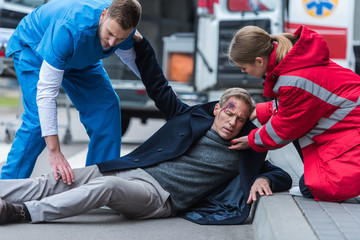 young male and female paramedics helping injured man on the street