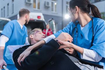 paramedics moving wounded mature man on ambulance stretcher