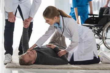 cropped image of doctors checking pulse of mature man lying on floor