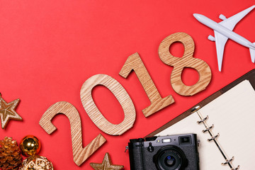 Travel concept on wooden table.Christmas decorations,camera, map and wooden numbers 2018