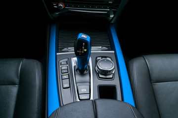 Blue Automatic gear stick (transmission) of a modern car, multimedia and navigation control buttons. Car interior details. Transmission shift.