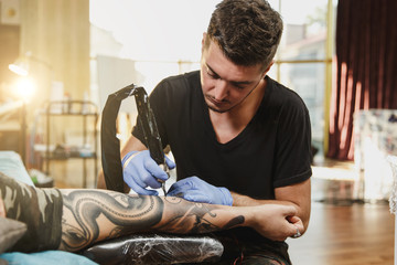 Professional tattooer artist doing picture on hand of man by machine black ink from a jar. Tattoo art on body. Equipment for making tattoo art. Master makes tattooed in light studio.