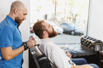 Male professional hairdresser serving client by protective tape. Ginger handsome stylish young man with big beard and short hair getting trendy haircut in black cape. Light white barber shop room.