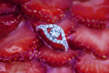 Engagement set of rings on the top of the sweet strawberry cake