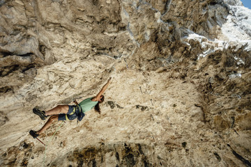 Front view of rock climber on a overhanging limestone cave