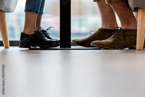 cropped image of father and daughter legs under table Stock photo