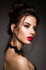 Gorgeous Young Brunette Woman face portrait. Beauty Model Girl with bright eyebrows, perfect make-up, red lips, touching her face. Sexy lady makeup for party.