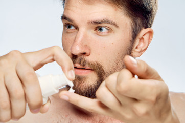 Man with beard on white background applies cosmetic cream, portrait