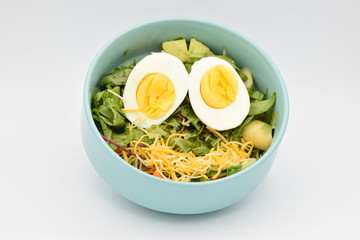 Green Salad in a Blue Bowl on White Backgroun