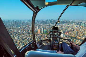 Helicopter cockpit inside the cabin flying above Tokyo skyline. Sumida District, Japan. Sunny day.