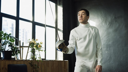 Young concentrated fencer man training fencing exercise in studio indoors