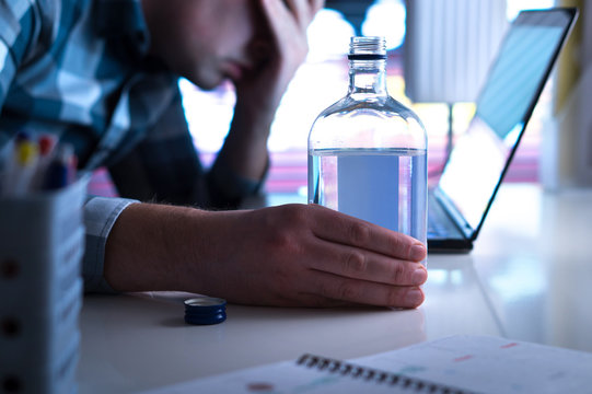 Alcoholism or drinking problem concept. Alcoholic with vodka bottle on table. Man and alcohol late at night. Drunk at work or in home office.