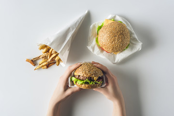 cropped view of hands with hamburgers and french fries in paper cone, isolated on white