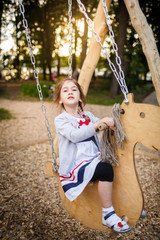 Cute little girl on a swing. Smiling child playing outdoors in summer.